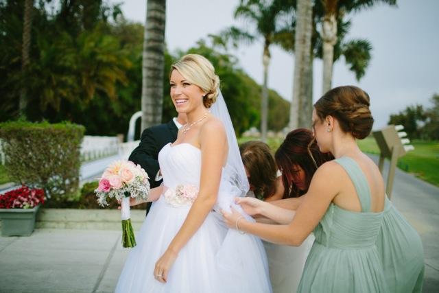 bridesmaids helping bride bustle dress