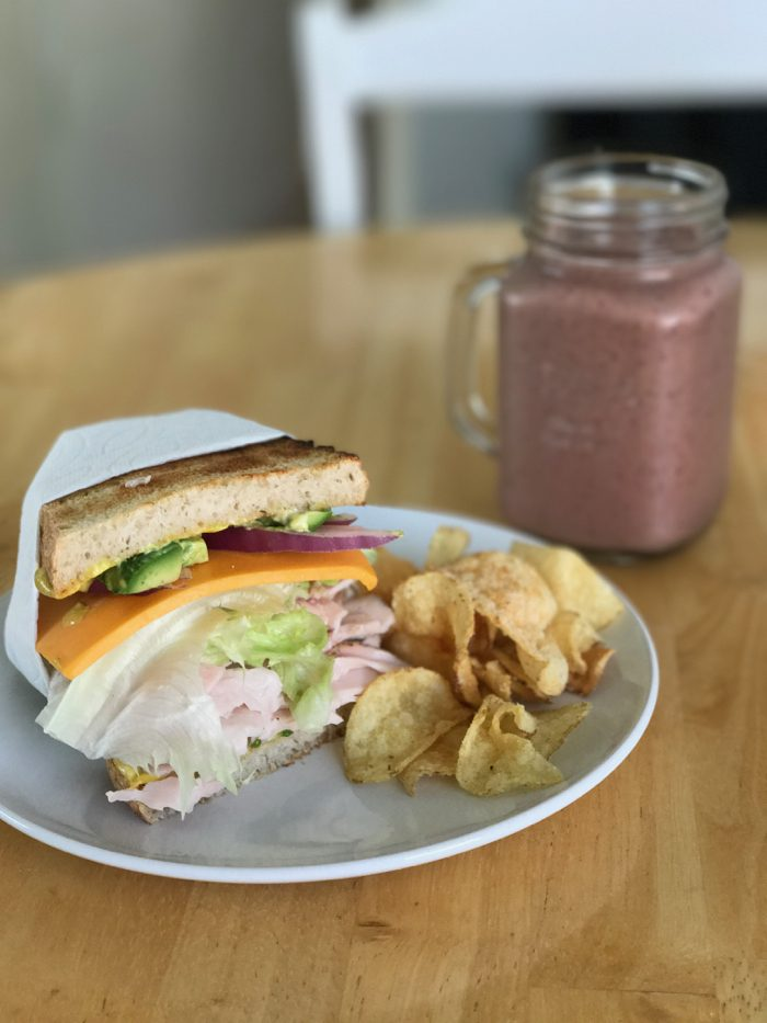 Turkey Sandwich on Toasted Sourdough With Turkey, Cheese, Avocado, Onion and Lettuce With Sea-Salt and Vinegar Kettle Chips and A Fruit/Spinach Smoothie